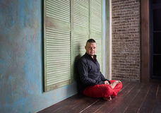 Portrait of a young man, black shirt and red slacks,lotus posture Royalty Free Stock Photos