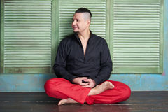 Portrait of a young man, black shirt and red slacks, lotus posture Stock Photography