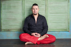 Portrait of a young man, black shirt and red slacks, lotus posture Royalty Free Stock Image