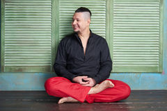 Portrait of a young man, black shirt and red slacks,  lotus posture. Portrait of a young man, black shirt and red slacks, hairstyle with shaved temples and Royalty Free Stock Photo