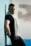 Portrait of a young man, in black slacks and a black T-shirt and. White scarf, hairstyle with shaved temples and slicked back hair at the head, different Royalty Free Stock Photos