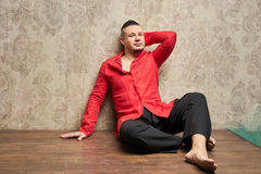 Portrait of a young man, in black slacks and a red shirt, hairst. Yle with shaved temples and slicked- back hair at the top of the head, emotions, beige wall Stock Images