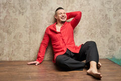 Portrait of a young man, in black slacks and a red shirt, sitting on the floor. Hairstyle with shaved temples and slicked- back hair at the top of the head Stock Images