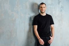 Portrait of a young man in a black T-shirt leaned against a vintage gray wall. Copy space. stock images