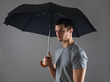 Portrait of a young man with a black umbrella. On a grey background Royalty Free Stock Photos