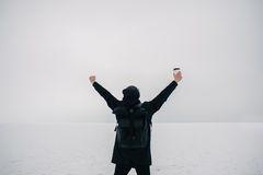 Portrait of a young man in black who winter on the frozen lake feels free. Portrait of a young man in black who winter on the frozen lake is experiencing freedom Stock Image