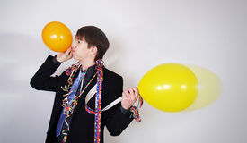 Portrait of young man blowing a balloon Stock Images