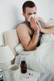 Portrait of a young man blowing his nose Stock Image