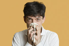 Portrait of a young man blowing nose over colored background Stock Photos