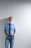 Portrait of young man in blue jeans. Guy holding hands in pocket and smiling Royalty Free Stock Photos