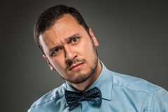 Portrait young man in blue shirt, looking with suspicion Stock Photo