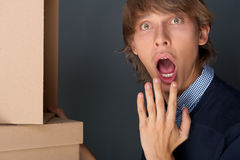 Portrait of young man with boxes. Against grey wall. He is afraid of starting new life royalty free stock image