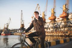 Young man with brown hair standing with bicycle and thoughtfully looking aside while talking on his mobile phone. Cool. Portrait of young man with brown hair Royalty Free Stock Photo