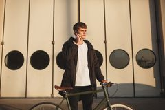 Young man with brown hair standing with classic bicycle and dreamily looking aside while talking on his cellphone. Portrait of young man with brown hair standing Stock Photo