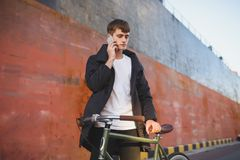 Young man with brown hair standing with classic bicycle and thoughtfully looking aside while talking on his cellphone. Portrait of young man with brown hair Royalty Free Stock Images