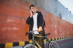 Young man with brown hair walking with classic bicycle and happily looking aside while talking on his cellphone. Smiling. Portrait of young man with brown hair Royalty Free Stock Image