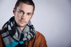 Portrait of  young man in brown jacket with striped scarf over gray background. Close-up. Royalty Free Stock Photos