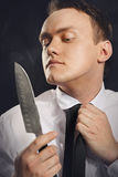 Portrait of a young man browsing in knife blade. Royalty Free Stock Images