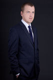 Portrait of young man in business suit over grey Royalty Free Stock Photos