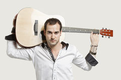 Portrait of young man carrying guitar over his shoulder against gray background Royalty Free Stock Photo