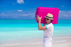 Portrait of a young man carrying his luggage on the beach Royalty Free Stock Image