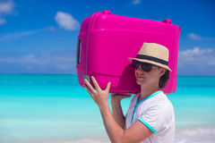 Portrait of a young man carrying his luggage on the beach Stock Image