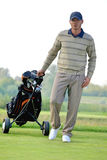 Portrait of young man carrying trolley with golf bag Royalty Free Stock Photography