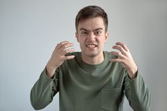 portrait of young man in casual clothes with a furious angry unhappy expression on his face bared teeth and hands outstretched in stock image