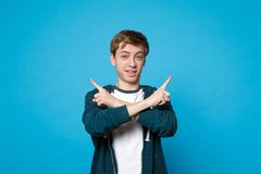 Portrait of young man in casual clothes holding hands crossed, pointing index fingers aside isolated on blue wall royalty free stock image