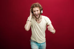 Portrait of young man in casual clothes listening to music via headphones with fist up.Red background.Isolate. Royalty Free Stock Image