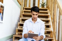Portrait of young man sitting at the stairs in office Stock Image