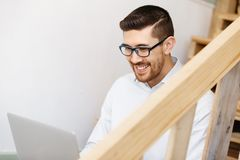 Portrait of young man sitting at the stairs in office Royalty Free Stock Images