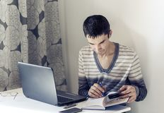 Portrait of young man In casual wear on the job working on laptop, making notes in notebook royalty free stock image