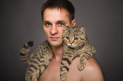 Portrait of a young man with a cat Stock Images