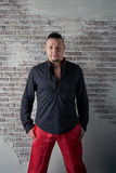 Portrait of a young man, chubby, dressed in red slacks and a black shirt. Hands in his pockets, fashionable hairstyle with shaved temples and slicked- back hair Royalty Free Stock Photos