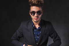 Portrait of young man closing his jacket while posing in dark s Royalty Free Stock Photos