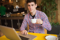 Portrait of young man with coffee using laptop Stock Photos