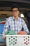 Portrait of young man with college dorm items in back of car, looking at camera Stock Image