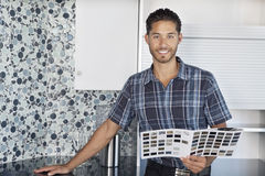 Portrait of young man with color samples standing in model home kitchen Royalty Free Stock Photo