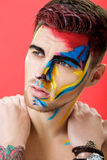 Portrait of young man with colored face paint on red background. Professional Makeup Fashion. fantasy art makeup Royalty Free Stock Photos