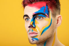 Portrait of young man with colored face paint on yellow background. Professional Makeup Fashion. fantasy art makeup Stock Image