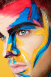 Portrait of young man with colored face paint on yellow background. Professional Makeup Fashion. fantasy art makeup Royalty Free Stock Photo