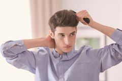 Portrait of young man combing his hair. Indoors Royalty Free Stock Image