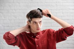 Portrait of young man combing his hair. On brick wall background Royalty Free Stock Photos