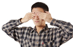 Portrait of a young man covering his eyes Stock Photo