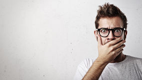 Portrait of a young man covering his mouth with hand Royalty Free Stock Photos