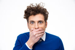 Portrait of a young man covering his mouth. Over white background Royalty Free Stock Image