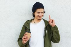 Portrait of young man with crisp hair and little beard, in casual anorak, black cap, holds takeaway coffee, pointing index finger. Up, isolated on white stock image