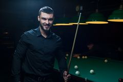 Portrait of young man with cue playing billiard Royalty Free Stock Photo
