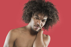 Portrait of a young man with curly hair over colored background Royalty Free Stock Photography
